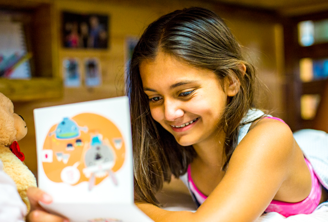 Smiling camper reads letter from home