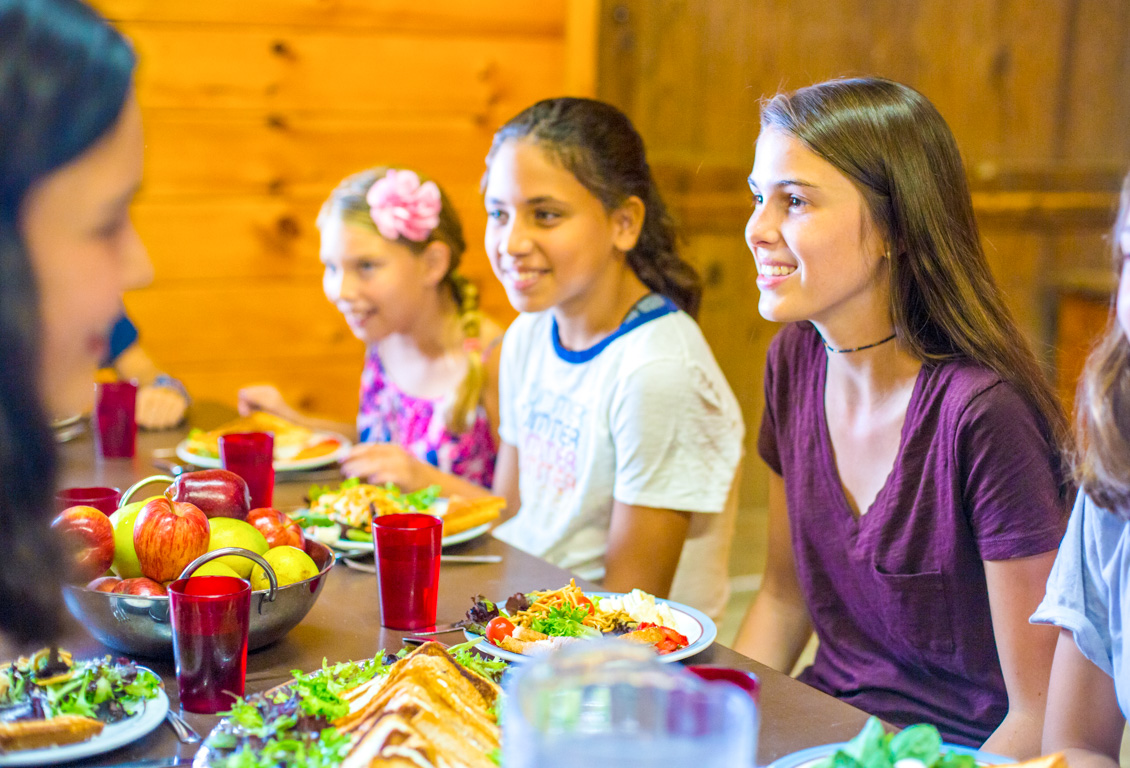 Campers eat meal in dining hall