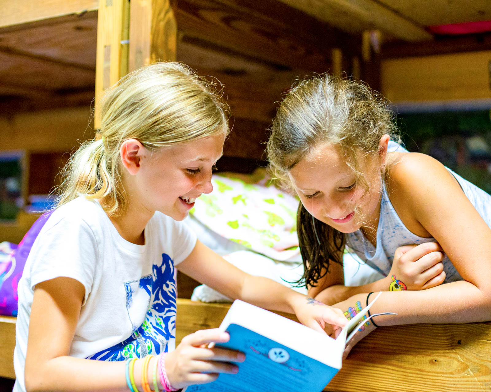 Girls read book together in summer camp bunk