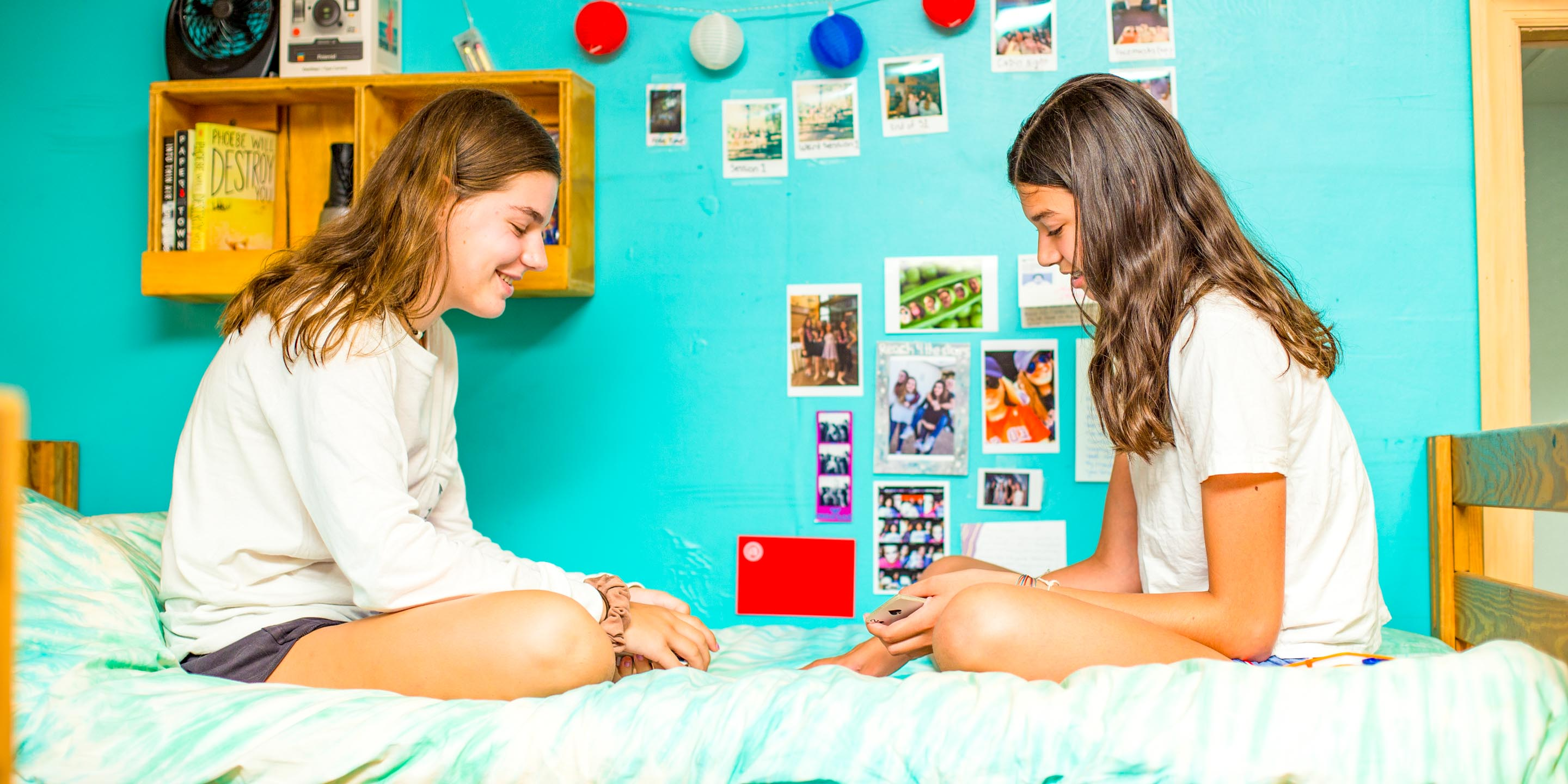 Girls play cards in cabin bunk at summer camp