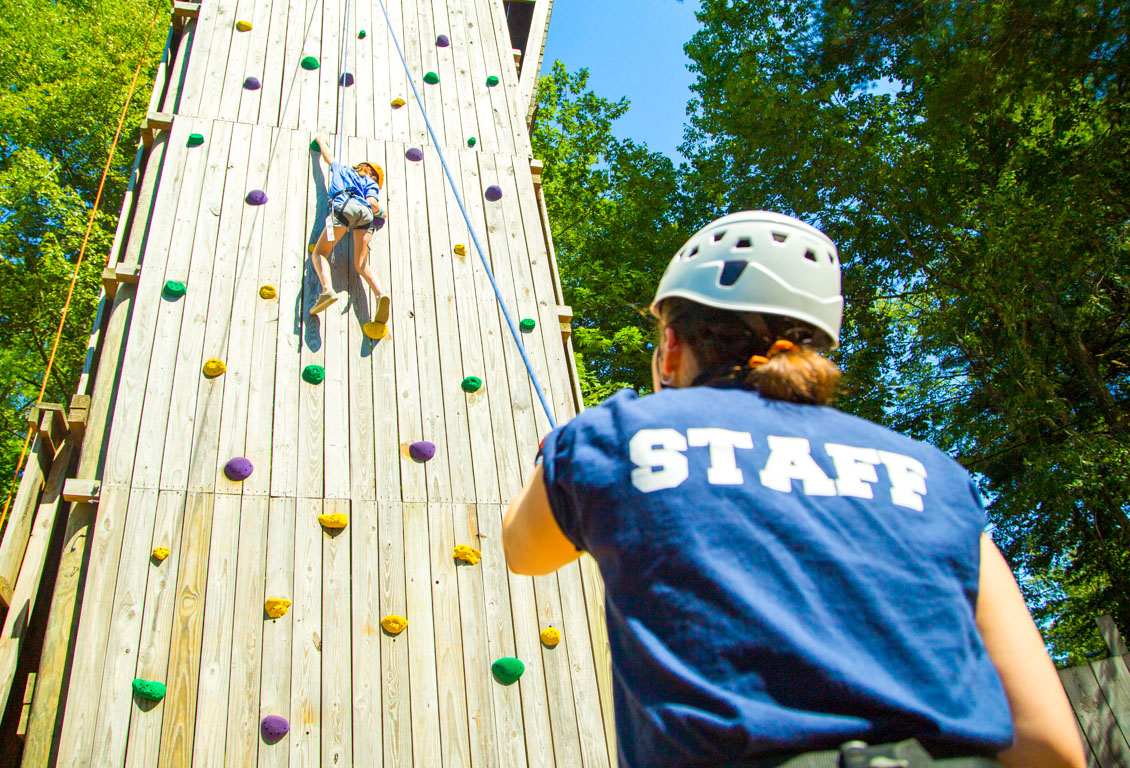 Camp staff belays for rock climbing camper