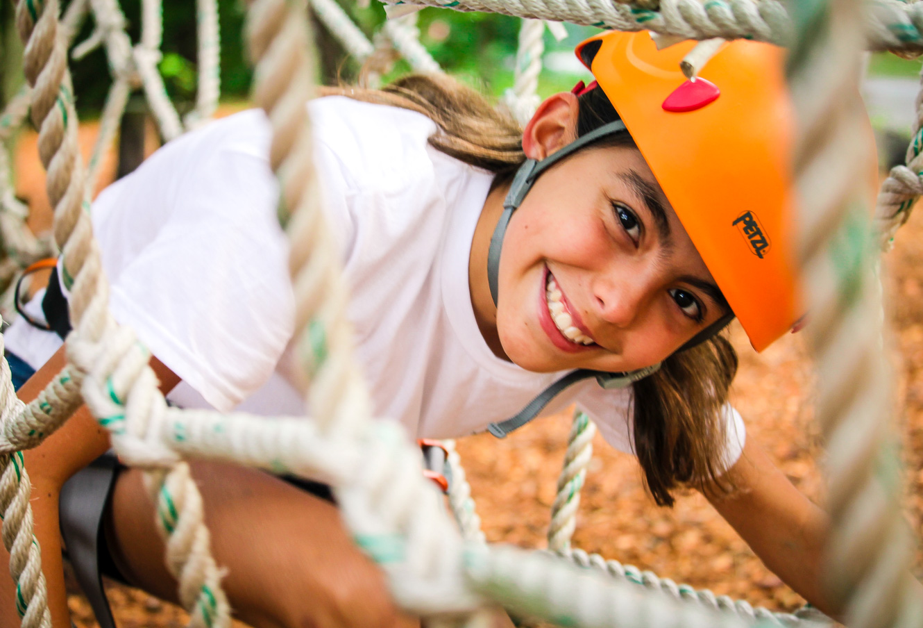 Girl crouches down in ropes course to smile at camera